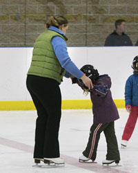 Young girl learning to skate with her mother